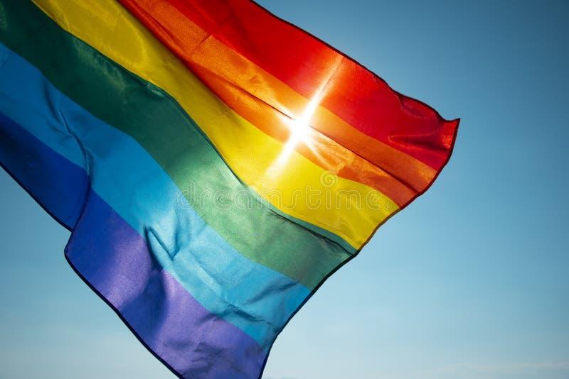 Bandeira do arco-íris que acena no céu azul fotografia de stock royalty free