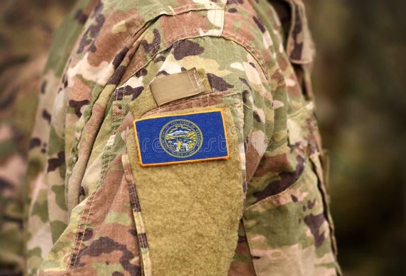 Bandeira do Estado de Nebraska sobre o uniforme militar Estados Unidos EUA, exército, soldados Colagem imagens de stock royalty free