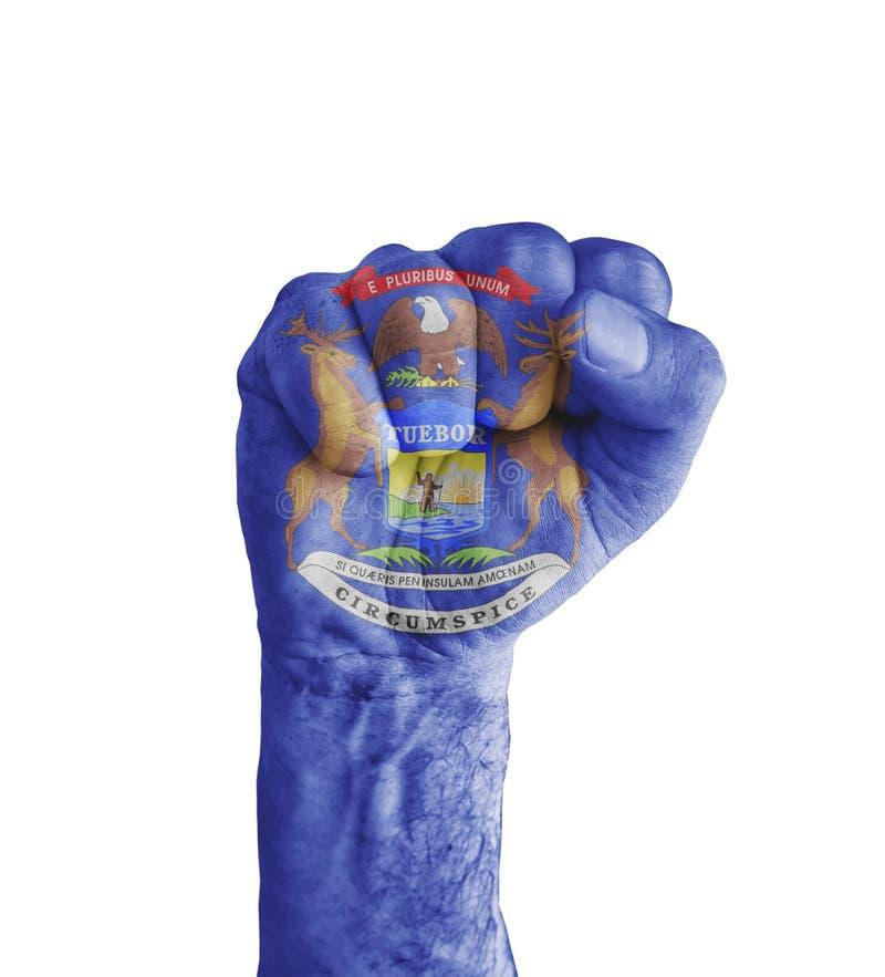 A bandeira do estado do Michigan dos E.U. pintada no punho humano gosta da vitória fotos de stock royalty free