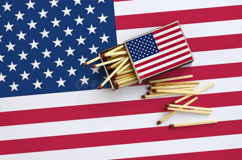 A bandeira do Estados Unidos da América é mostrada em uma caixa de fósforos aberta, de que diversos fósforos caem e mentiras em u imagem de stock royalty free