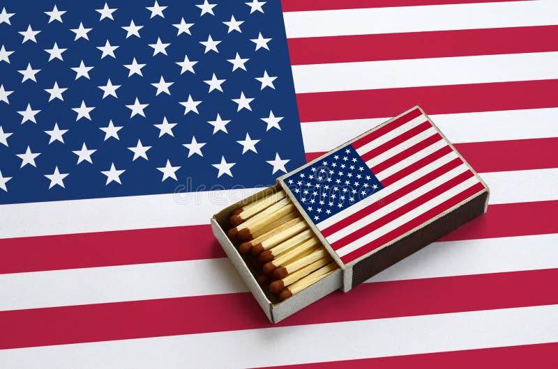 A bandeira do Estados Unidos da América é mostrada em uma caixa de fósforos aberta, que seja enchida com os fósforos e se encontr imagens de stock