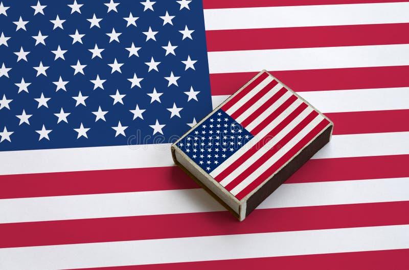 A bandeira do Estados Unidos da América é representada em uma caixa de fósforos que se encontre em uma grande bandeira imagens de stock