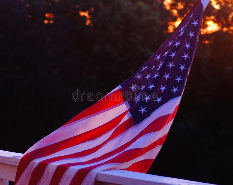 Bandeira do Estados Unidos que incandesce sob um por do sol fotos de stock