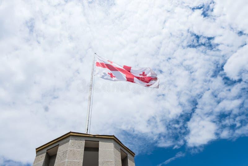 A bandeira do Ge?rgia com c?u azul e nuvens imagem de stock royalty free