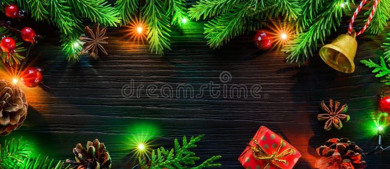 Bandeira do Natal Festão da árvore de abeto com as decorações de incandescência da árvore de Natal na placa de madeira preta imagem de stock royalty free