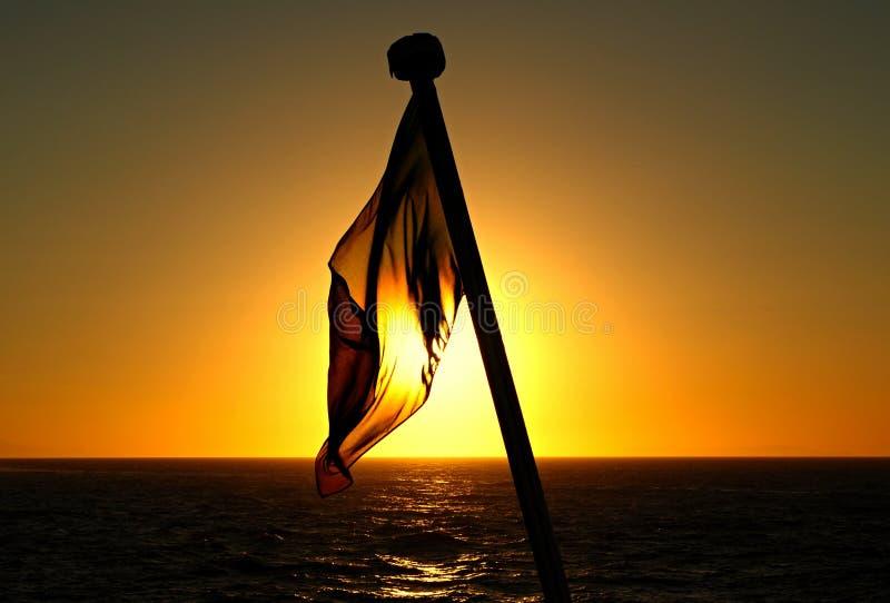 A bandeira do navio no por do sol fotos de stock royalty free