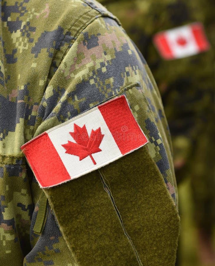 Bandeira do remendo de Canadá no braço dos soldados foto de stock
