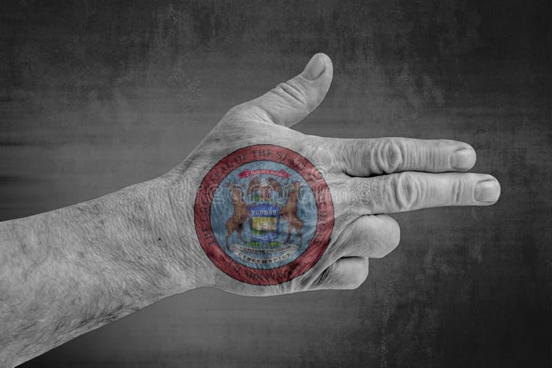 Bandeira do selo de Michigan do estado de E.U. pintada na mão masculina como uma arma ilustração royalty free