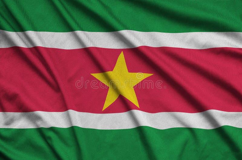A bandeira do Suriname é descrita em uma tela de pano dos esportes com muitas dobras Bandeira da equipe de esporte fotografia de stock