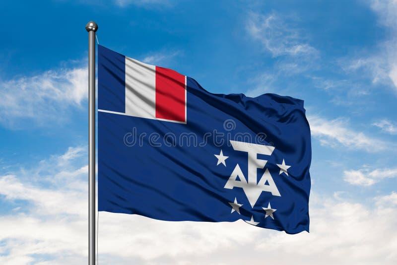 Bandeira do território dos Territórios Franceses do Sul que acenam no vento contra o céu azul nebuloso branco foto de stock
