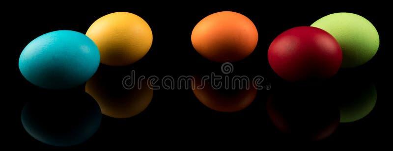 Bandeira dos ovos da páscoa Ovos da páscoa coloridos no fundo preto com reflexão Projeto moderno imagem de stock