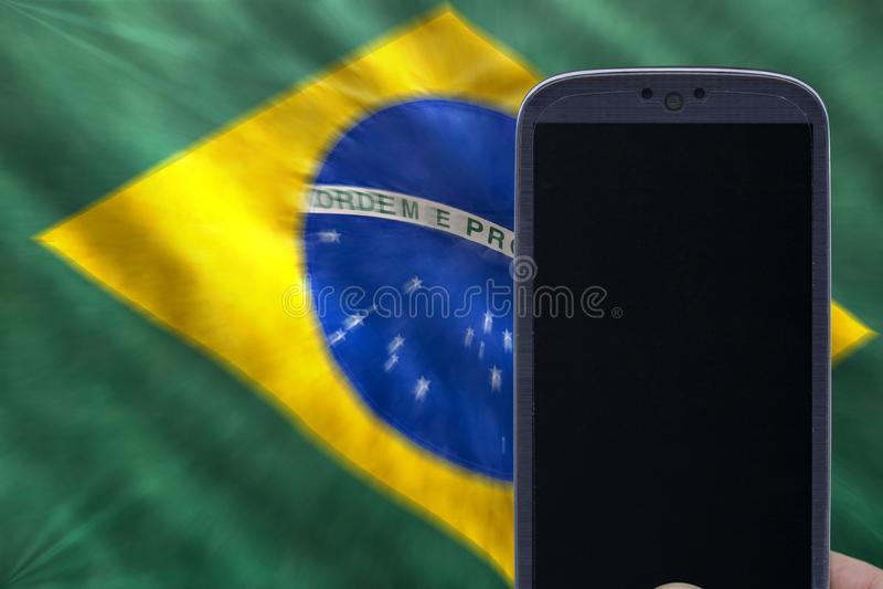Bandeira e smartphone brasileiros para o campeonato do mundo e o jogo brasileiro foto de stock royalty free