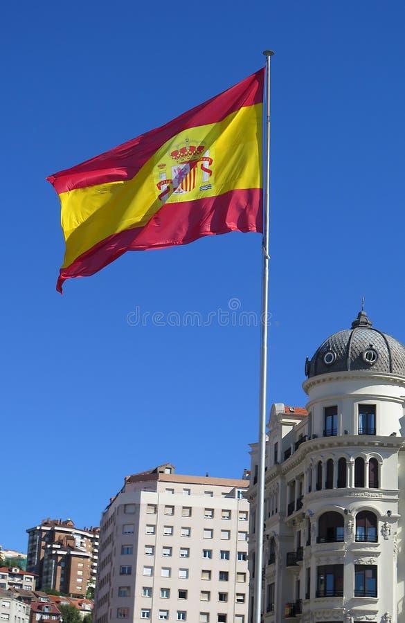 Bandeira espanhola que voa sobre a cidade, sob um céu azul claro fotografia de stock royalty free