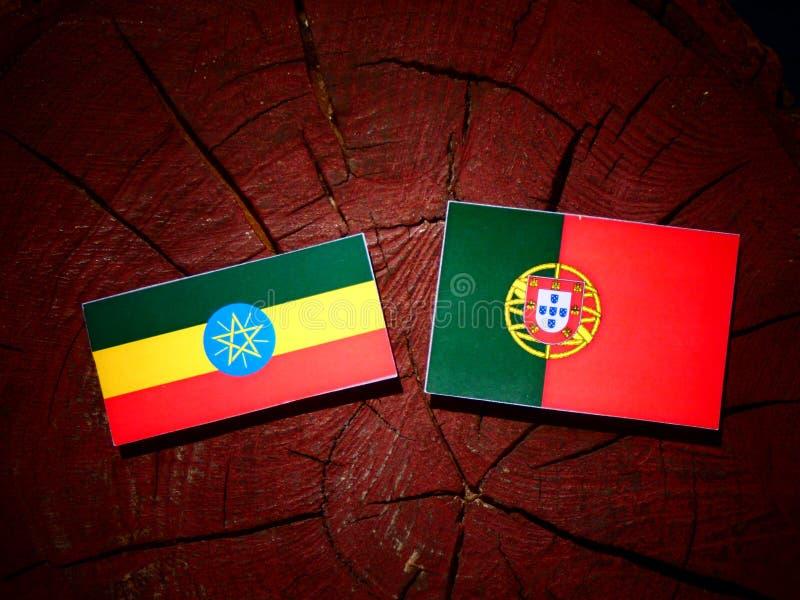 Bandeira etíope com bandeira portuguesa em um coto de árvore isolado foto de stock