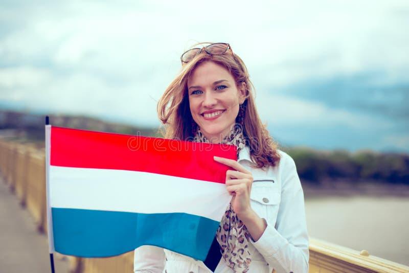 Bandeira feliz da terra arrendada da jovem mulher de Países Baixos na ponte fotografia de stock