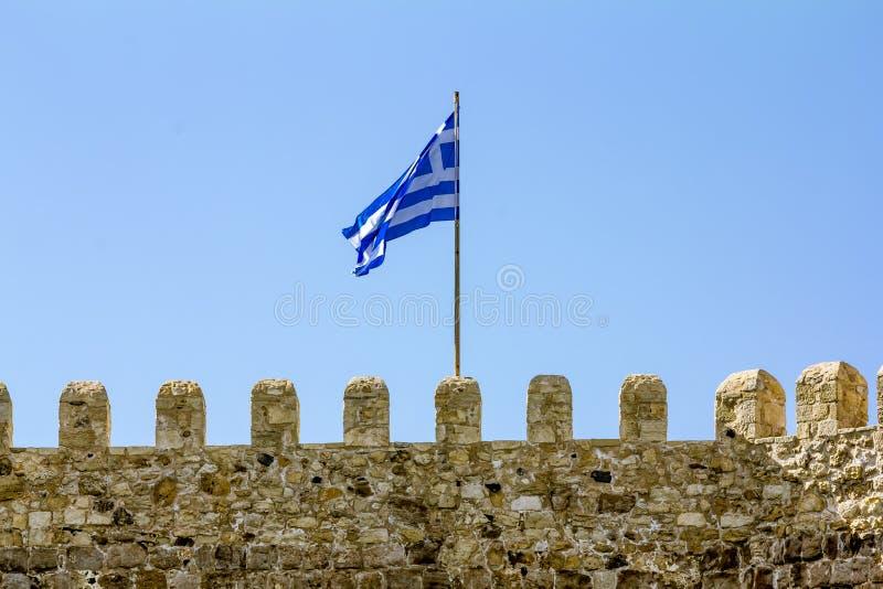 A bandeira grega vibra na parede da fortaleza Venetian na cidade de Rethymno em Grécia imagens de stock