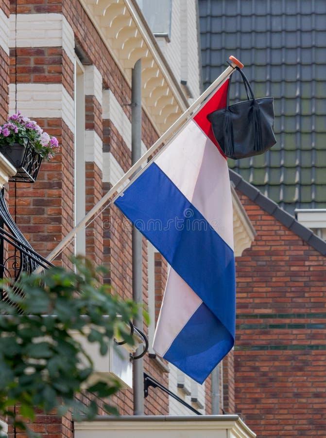 Bandeira holandesa com sacola, saco de escola, uma tradição quando um estudante comemorar a graduação fotos de stock