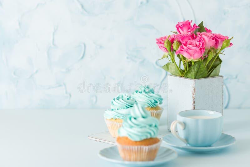 Bandeira horisontal pastel azul com queques decorados, copo do coffe com leite e ramalhete de rosas cor-de-rosa fotos de stock royalty free