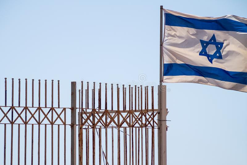 Bandeira israelita voando perto de uma cerca num dia céu limpo imagem de stock royalty free