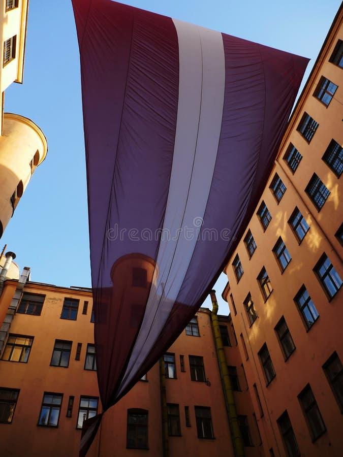 Bandeira letão enorme entre construções velhas imagens de stock royalty free