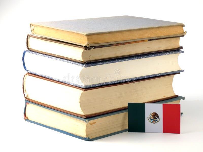 Bandeira mexicana com a pilha dos livros no fundo branco fotografia de stock