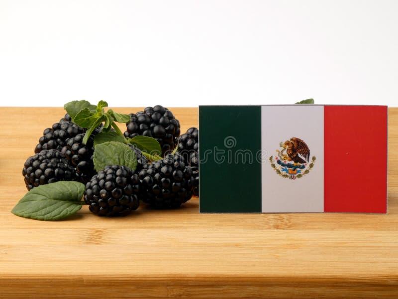 Bandeira mexicana em um painel de madeira com as amoras-pretas isoladas em um w imagens de stock