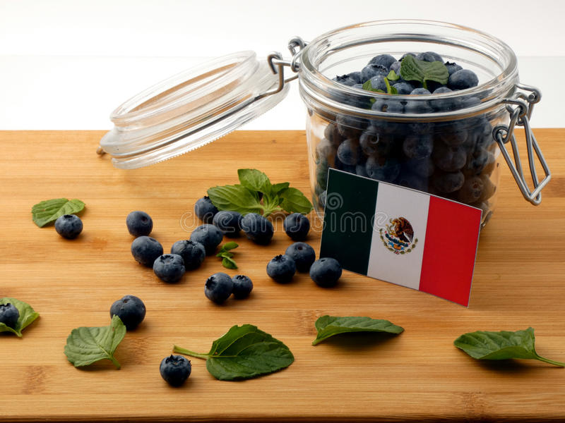 Bandeira mexicana em uma prancha de madeira com os mirtilos no whit fotografia de stock