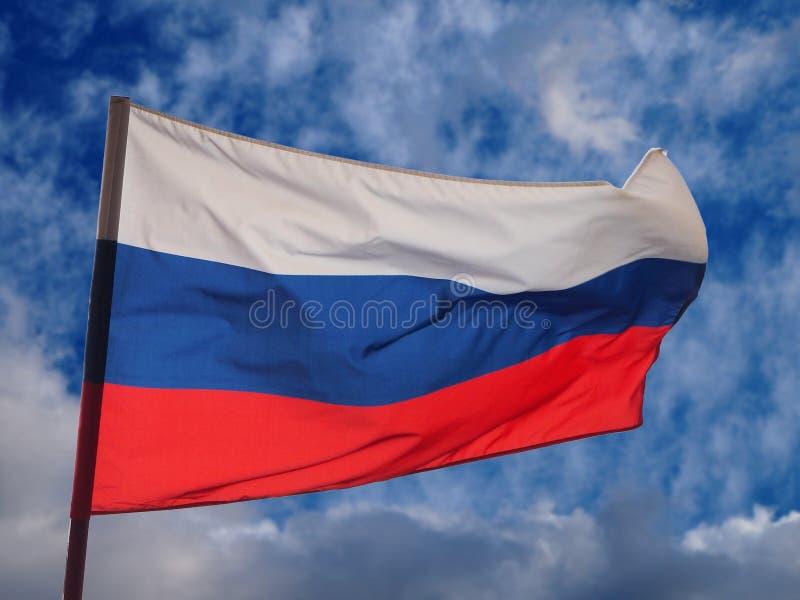 A bandeira nacional da Federação Russa que acena no vento nos nuvems tempestuosa e no fundo do céu azul imagem de stock