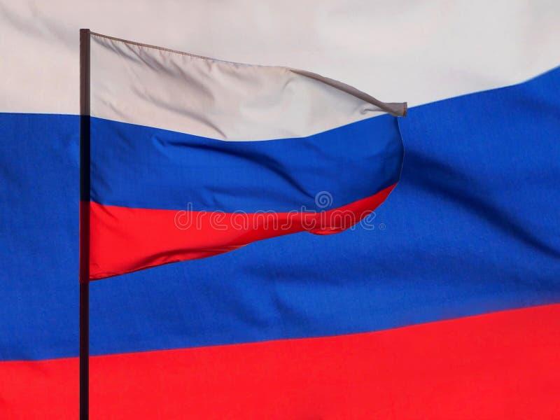 A bandeira nacional da Federação Russa que acena no vento, sincronizada com a textura tricolor da tela no fundo fotografia de stock