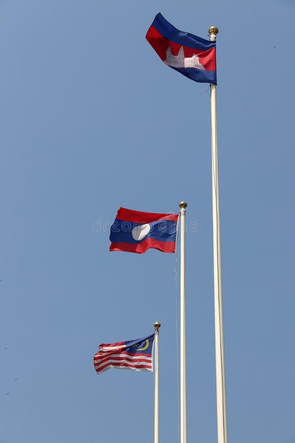 Bandeira nacional de Camboja, de Laos e de Malásia no fundo brilhante do céu azul Fundido afastado pelo vento foto de stock