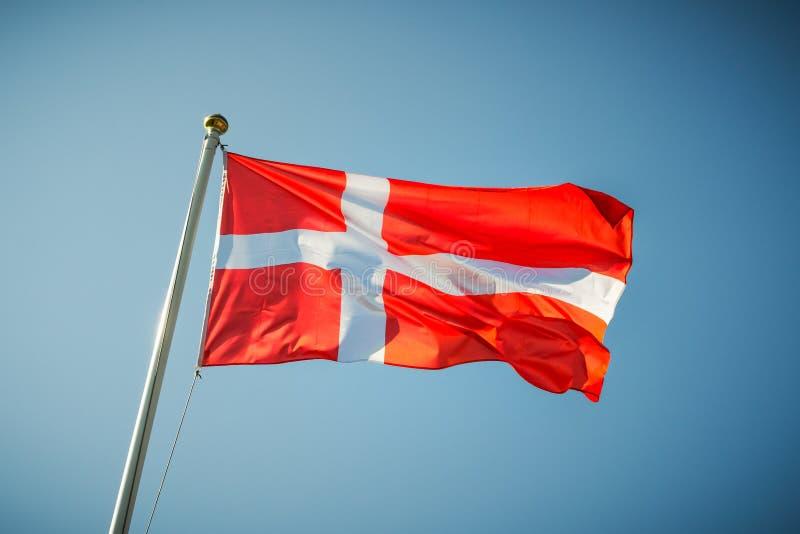 Bandeira nacional de Dinamarca que acena em um céu azul imagem de stock royalty free