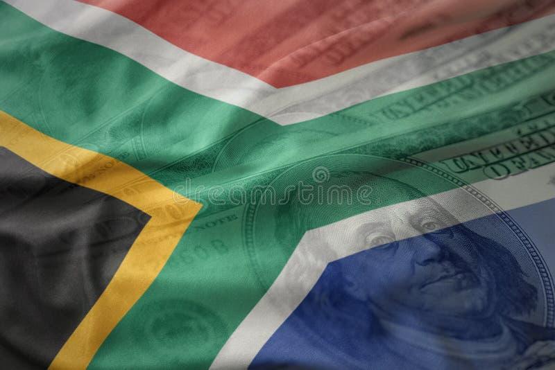 Bandeira nacional de ondulação colorida de África do Sul em um fundo americano do dinheiro do dólar foto de stock