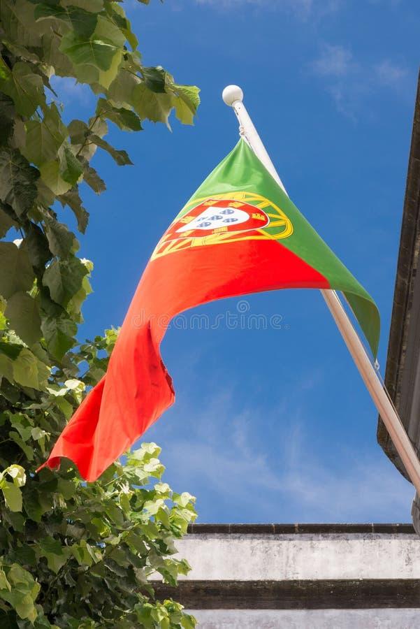 A bandeira nacional de Portugal torna-se no vento contra um céu azul imagem de stock