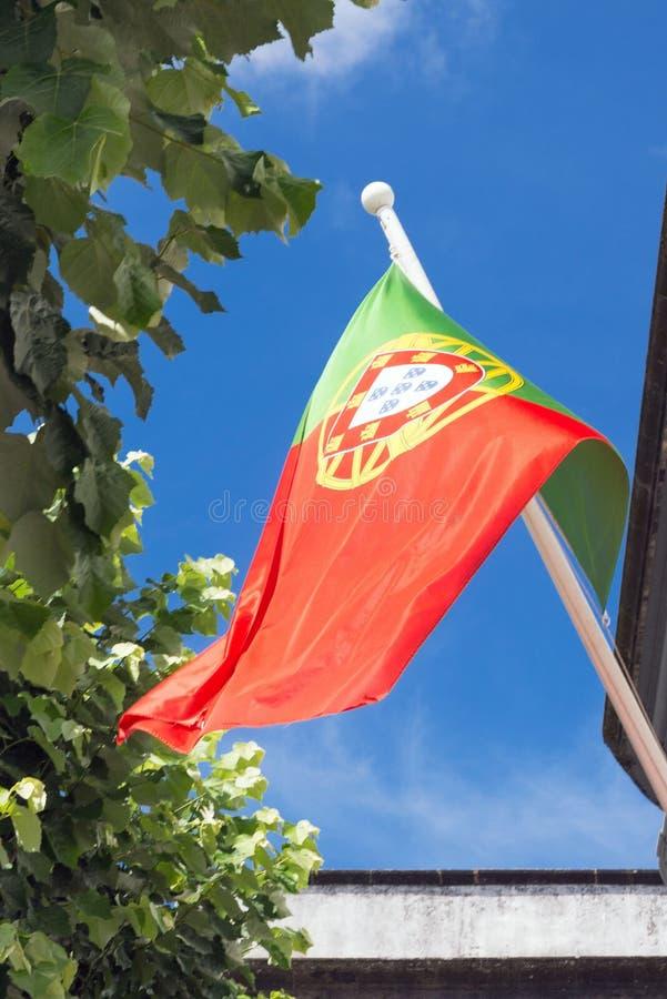 A bandeira nacional de Portugal torna-se no vento contra um céu azul imagens de stock