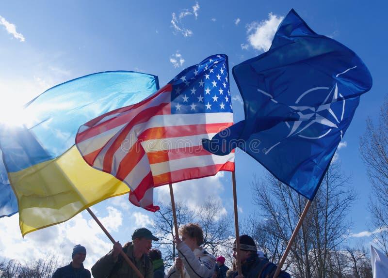 A bandeira nacional de Ucrânia e do Estados Unidos e a bandeira da OTAN estão vibrando contra o céu azul imagem de stock royalty free
