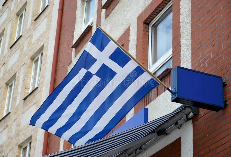 A bandeira nacional do Hellenic Republic vibra em uma fachada da construção fotos de stock