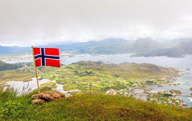 Bandeira nacional norueguesa no vento na parte superior do pico de Nonstinden com o fiorde no fundo, Ballstad, a municipalidade d fotografia de stock royalty free