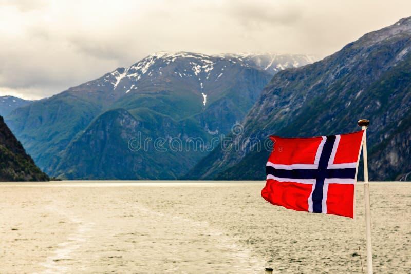 Bandeira nacional norueguesa que acena no vento no fiorde de Sogne com as montanhas no fundo, Aurlan, condado de Fjordane do og d imagem de stock