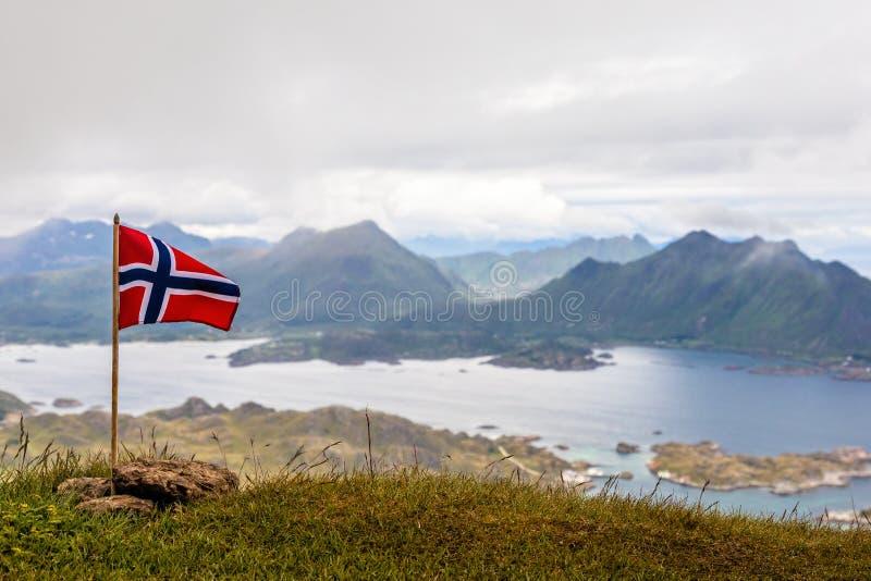 Bandeira nacional norueguesa que renuncia no vento na parte superior do pico de Nonstinden com o fiorde no fundo, Ballstad, Vestv imagem de stock