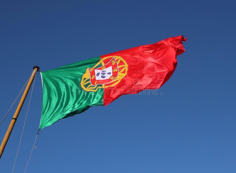 Bandeira nacional portuguesa contra o céu azul imagens de stock