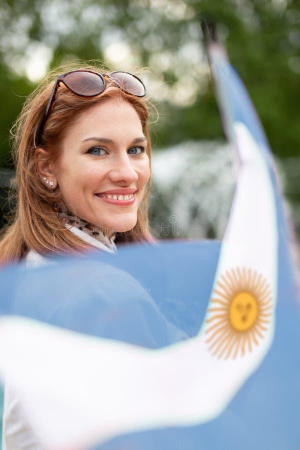 Bandeira natural nova feliz da terra arrendada da mulher de Argentina no parque imagem de stock royalty free