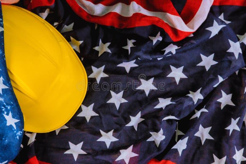 Bandeira patriótica dos EUA do americano feliz do Dia do Trabalhador e capacete amarelo imagem de stock