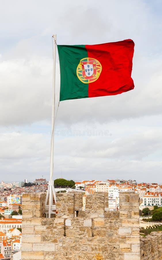 A bandeira portuguesa é representada sobre o Sao Jorge Castle imagens de stock
