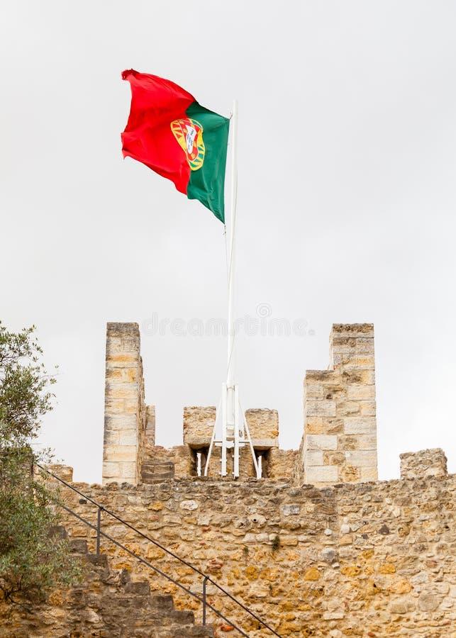 A bandeira portuguesa é representada sobre o Sao Jorge Castle imagem de stock