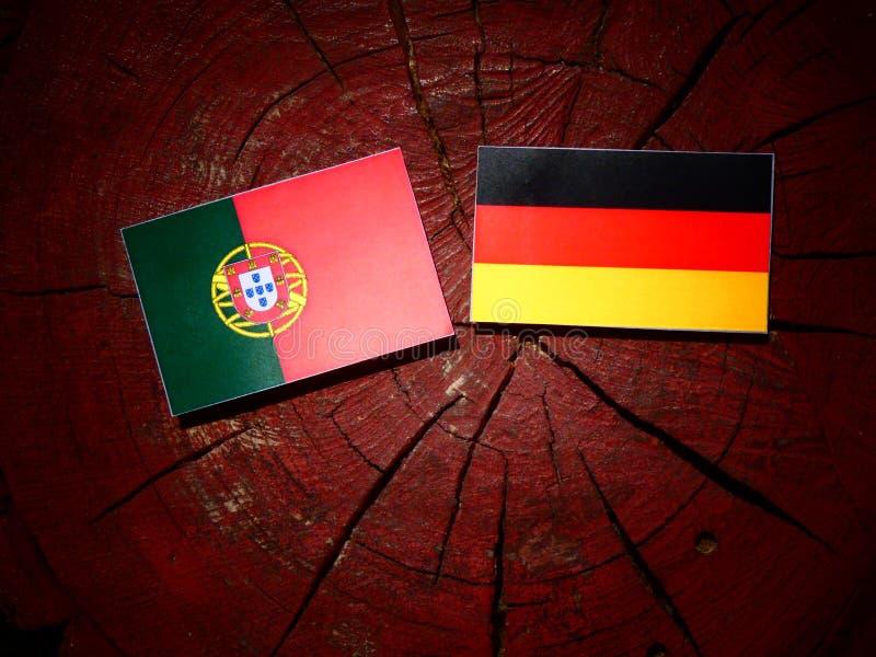 Bandeira portuguesa com bandeira alemão em um coto de árvore imagens de stock