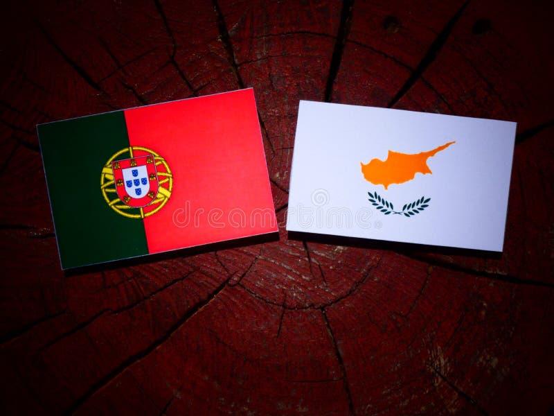 Bandeira portuguesa com bandeira cipriota em um coto de árvore isolado foto de stock royalty free