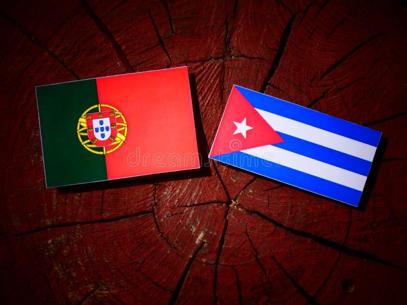 Bandeira portuguesa com bandeira cubana em um coto de árvore isolado foto de stock royalty free
