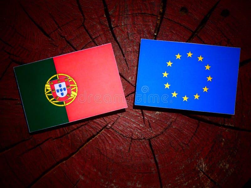 Bandeira portuguesa com bandeira da UE em um coto de árvore isolado imagens de stock royalty free