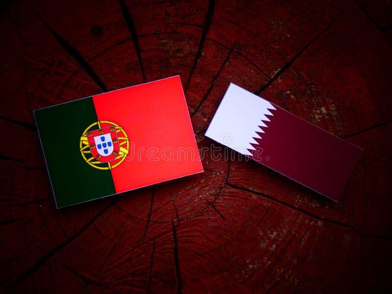 Bandeira portuguesa com bandeira de Qatari em um coto de árvore isolado imagens de stock