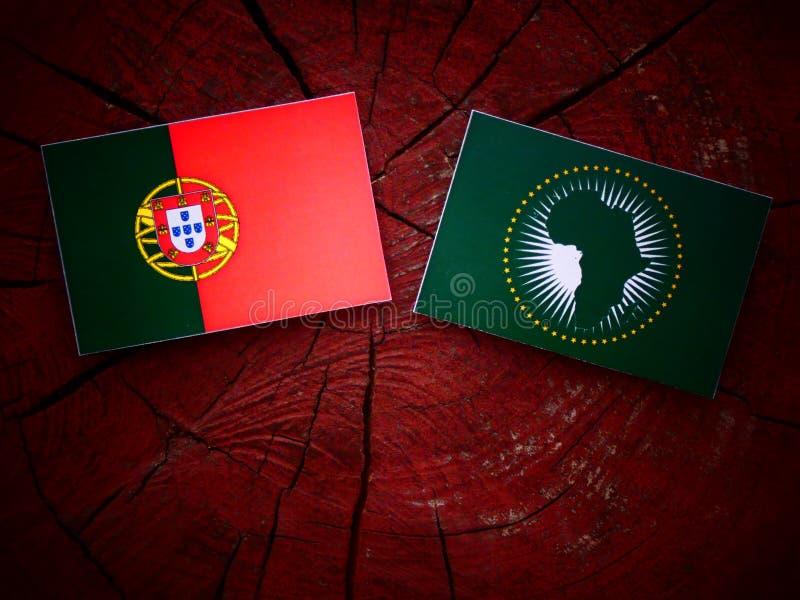 Bandeira portuguesa com a bandeira de união africana em um coto de árvore imagens de stock royalty free